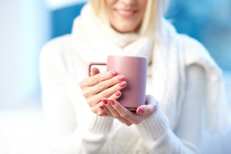 a pink porcelain cup in female hands photo