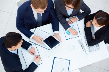 Group of business partners looking at touchscreen while planning work at meeting photo