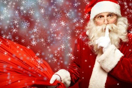 산타 클로스: 자신의 입으로 큰 빨간 자루 유지 집게 손가락으로 산타 클로스의 초상화 카메라를 찾고