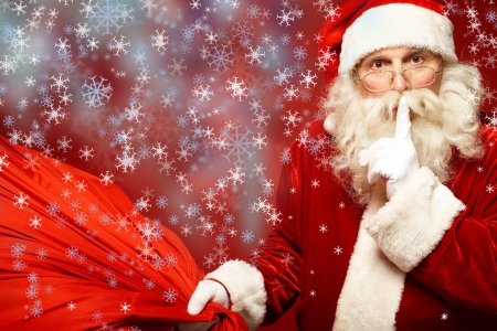 secret: Portrait of Santa Claus with huge red sack keeping forefinger by his mouth and looking at camera Stock Photo