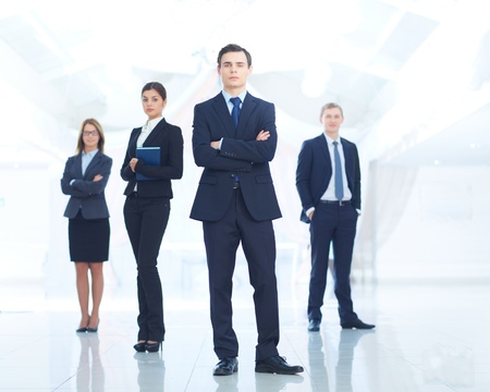 Portrait of young businessman looking at camera with elegant partners on background photo