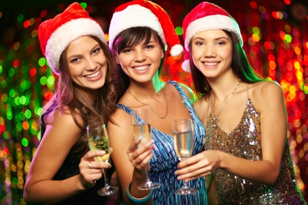 cheerful girls looking at camera with smiles while enjoying Christmas party