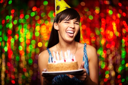 dinner party people: Portrait of funny girl with birthday cake grimacing and looking at camera at party