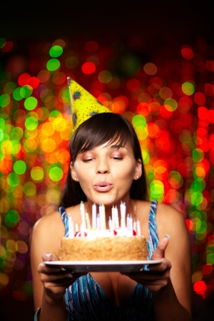 torta con candeline: Ritratto della bella ragazza in possesso di torta di compleanno e soffiando candele alla festa