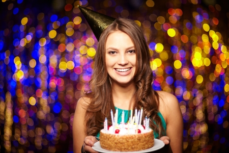 dinner party people: Portrait of joyful girl holding birthday cake and looking at camera at party Stock Photo