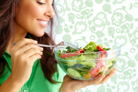 woman eat: Close-up of pretty girl eating fresh vegetable salad
