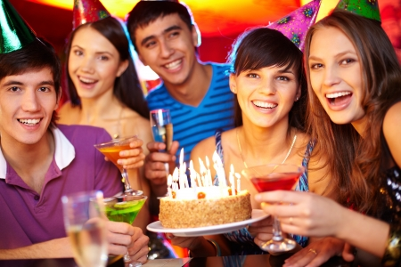 fiesta amigos: Retrato de los amigos alegres brindis y mirando a la c�mara en la fiesta de cumplea�os Foto de archivo