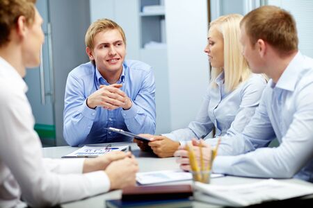 focus group: Image of handsome leader listening to employees at meeting Stock Photo