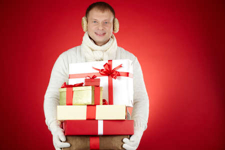 Portrait of happy man in white winterwear with stack of giftboxes looking at camera Stock Photo - 16221829