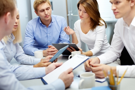 focus group: Image of several employees discussing new ideas in groups at meeting