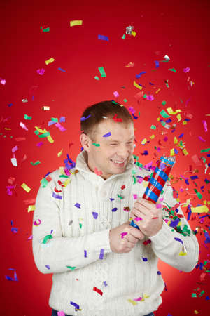 petard: Portrait of joyful man in white pullover having fun with confetti cracker Stock Photo