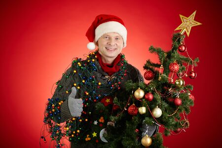 Portrait of happy man in Santa cap decorated xmas tree showing thumb up photo