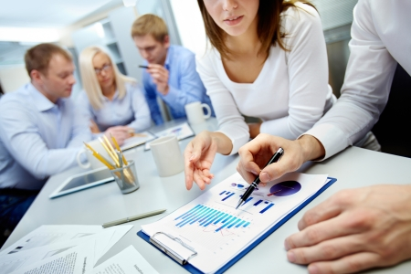 Close-up of business partners hands over document with their colleagues working on background Stock Photo - 16221779
