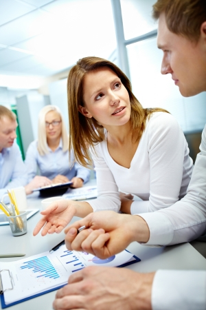 Vertical image of business partners discussing document with their colleagues working on background Stock Photo - 16221783