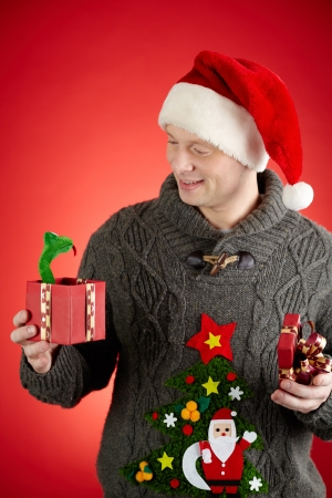 Portrait of happy man in Santa cap looking at toy snake in open giftbox Stock Photo - 16221848