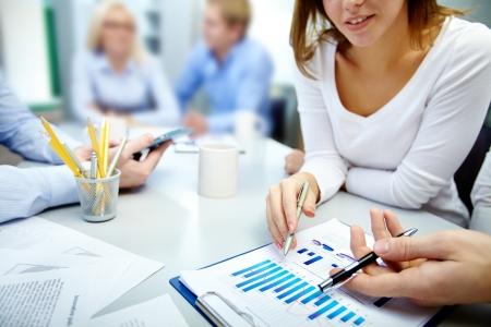 ambiente laboral: Primer plano de socios de negocios manos sobre el documento de trabajo con sus colegas en el fondo