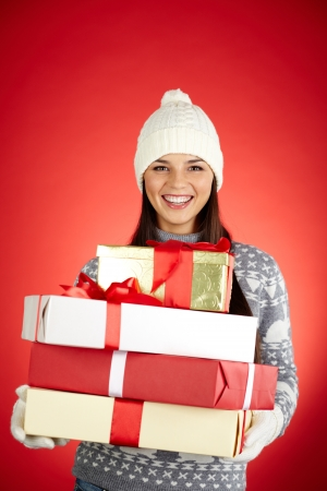 Portrait of happy girl with stack of giftboxes looking at camera photo