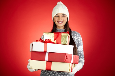 Portrait of happy girl with stack of giftboxes looking at camera Stock Photo