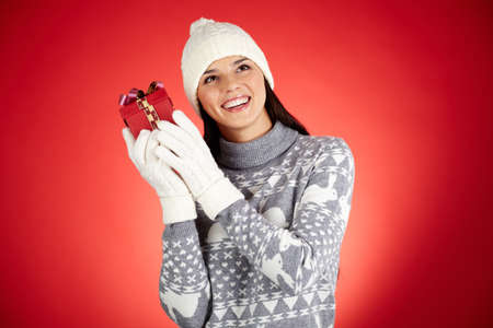 Portrait of happy girl in winterwear holding giftbox by her ear Stock Photo - 16221867