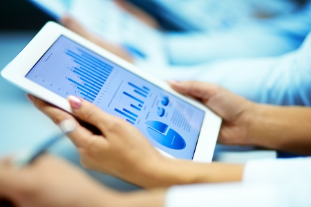 recursos financieros: Empresaria con las manos touchpad mientras se aprende situaci�n del mercado Foto de archivo