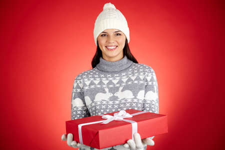 Portrait of happy girl in winterwear holding red giftbox and looking at camera Stock Photo - 16304956