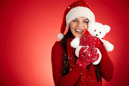 Joyful girl in Santa cap with white teddy bear looking at camera Stock Photo - 16304961