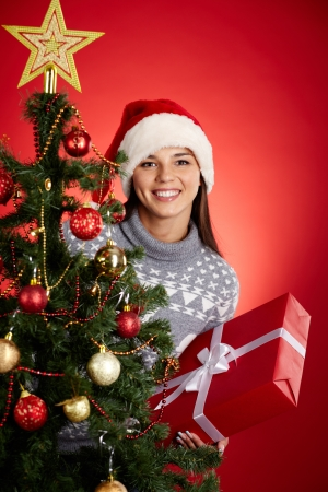 Portrait of happy girl holding red giftbox and looking at camera out of decorated firtree Stock Photo - 16221862