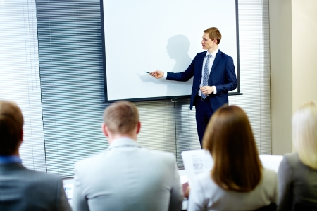 Confident businessman pointing at whiteboard while making speech at conference photo