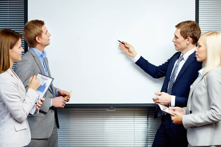 Confident businessman pointing at whiteboard while making speech at meeting Stock Photo - 16221813
