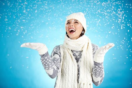 Joyful girl in winterwear enjoying snowfall photo