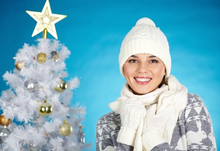 Joyful girl in winterwear looking at camera with decorated firtree behind Stock Photo - 16221837