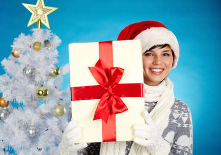 Joyful girl in Santa cap holding giftbox and looking at camera with decorated firtree behind Stock Photo - 16221834