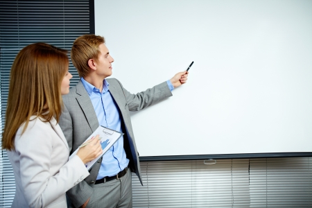 Confident businessman pointing at whiteboard while making speech with smart secretary near by Stock Photo - 16221772