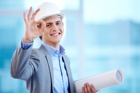 Portrait of cheerful architect signing okay and looking at camera photo