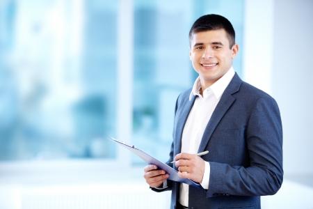 hombre escribiendo: Retrato de hombre de negocios alegre tomando notas y mirando a la c�mara Foto de archivo