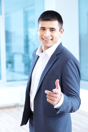 Portrait of cheerful businessman pointing and looking at camera Stock Photo - 16333938