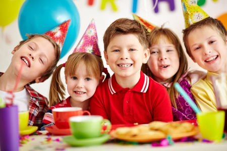 children party: Group of adorable kids looking at camera while having fun at birthday party