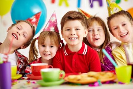 enfants qui rient: Groupe de gosses adorables regardant la cam�ra tout en s'amusant � la f�te d'anniversaire
