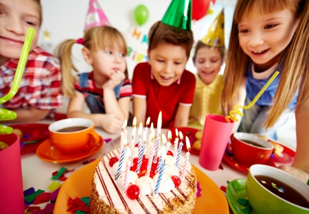 children party: Group of adorable kids looking at birthday cake with candles