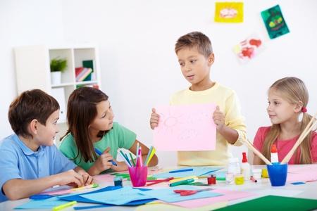 niños estudiando: Niño pequeño que muestra su dibujo a sus amigos en el aula