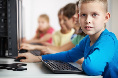 lad: Portrait of smart lad looking at camera at computer lesson Stock Photo