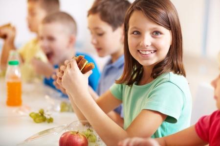 niños en la escuela: Grupo de compañeros de clase que tienen el almuerzo durante las vacaciones, con especial atención en la muchacha que sonríe con el sándwich