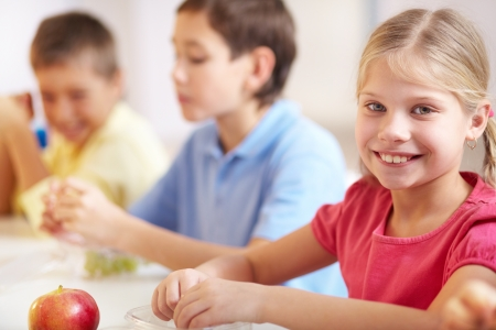 school lunch: Group of kids having lunch during break with focus on smiling girl looking at camera