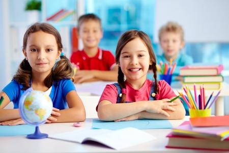 niños en la escuela: Retrato de dos niñas diligentes mirando a la cámara en el lugar de trabajo con los escolares en el fondo