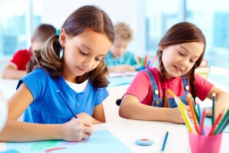 ni�os en la escuela: Retrato de muchachas encantadoras dibujo en el lugar de trabajo con los escolares en el fondo