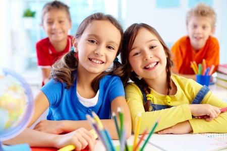 diligente: Retrato de dos ni�as diligentes mirando a la c�mara en el lugar de trabajo con los escolares en el fondo