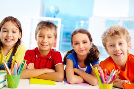 school friends: Group of diligent schoolchildren looking at camera in school Stock Photo