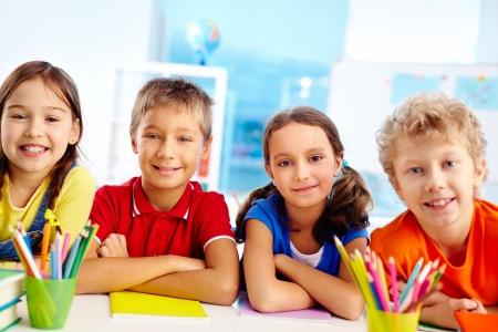 Group of diligent schoolchildren looking at camera in school Stock Photo