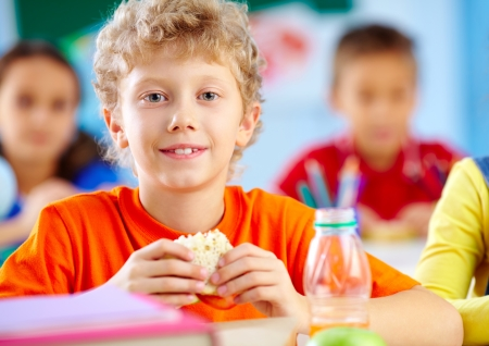 children eating: Cheerful schoolboy looking at camera while having lunch during break with his classmates behind