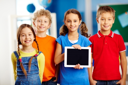 Portrait of smart schoolkids standing in line and looking at camera photo